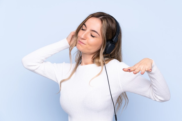 Jeune, femme, isolé, bleu, mur, écoute, musique, danse