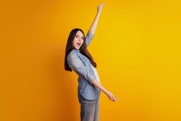 Jeune femme isolé sur fond jaune holding copyspace mesurer la taille