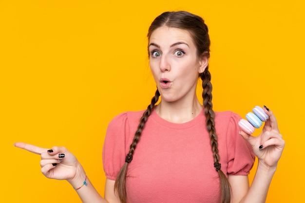 Jeune, femme, isolé, jaune, mur, tenue, coloré, français, macarons, pointage, côté