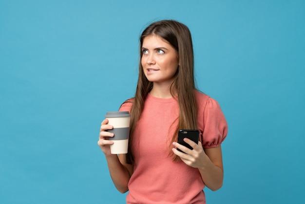 Jeune femme, isolé, mur bleu, tenue, café, emporter, mobile, penser quelque chose