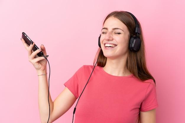 Jeune, femme, isolé, rose, mur, écoute, musique, faire, guitare, geste