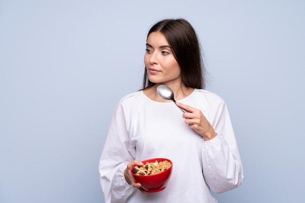Jeune femme sur isolé tenant un bol de céréales et de penser
