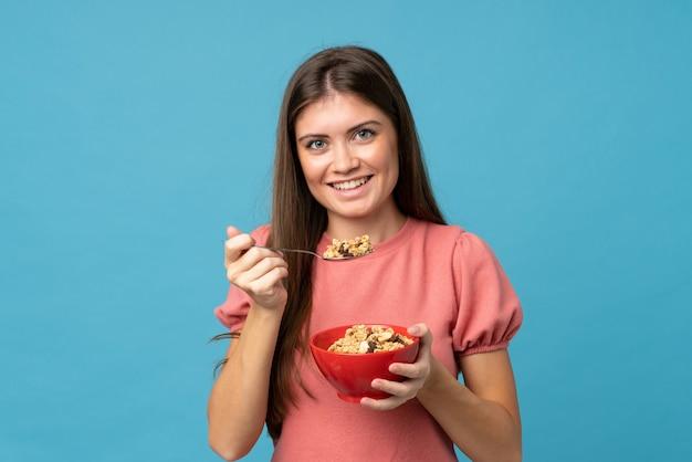 Jeune femme sur isolé tenant un bol de céréales
