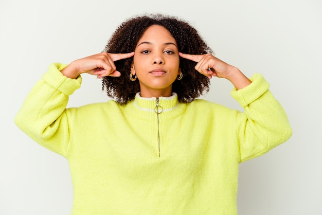 Jeune femme isolée axée sur une tâche, gardant l'index pointant la tête