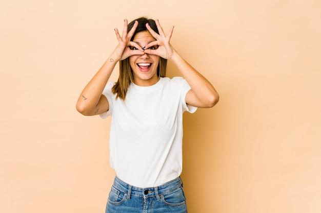 Jeune femme isolée sur beige excité en gardant le geste ok sur les yeux.