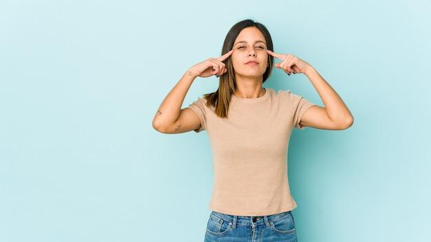 Jeune femme isolée sur bleu concentré sur une tâche, gardant l'index pointant la tête.