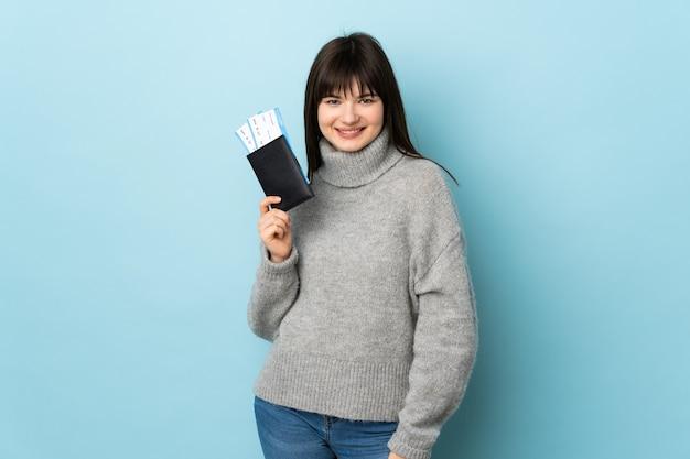 Jeune femme isolée sur bleu heureux en vacances avec passeport et billets d'avion