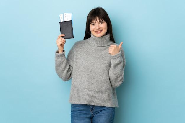 Jeune femme isolée sur bleu en vacances tenant un passeport et un avion avec le pouce vers le haut