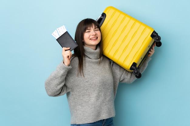 Jeune femme isolée sur bleu en vacances avec valise et passeport