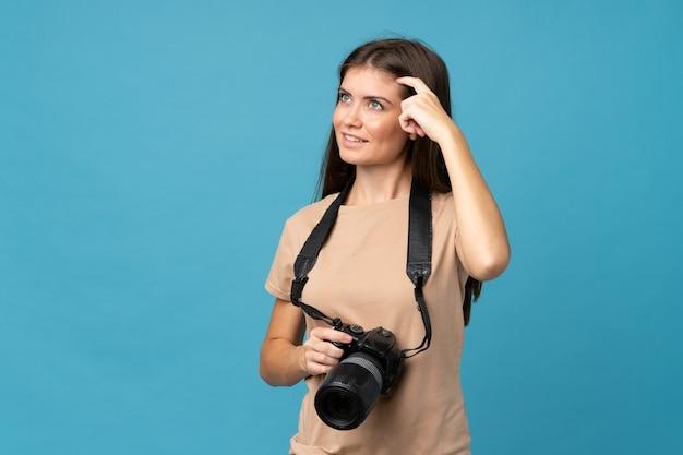 Jeune femme sur isolée avec une caméra professionnelle et pensant