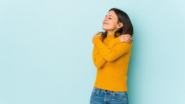 Jeune femme isolée sur fond bleu câlins, souriant insouciant et heureux.