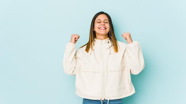 Jeune femme isolée sur fond bleu célébrant une victoire, passion et enthousiasme, expression heureuse.