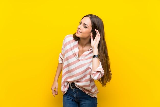 Jeune femme isolée sur jaune écoutant quelque chose en mettant la main sur l'oreille