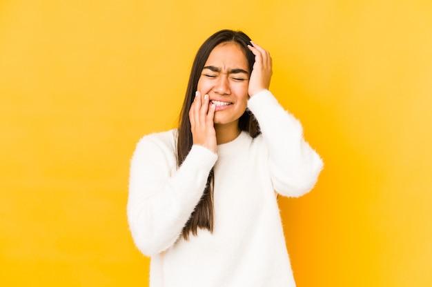 Jeune femme isolée sur un jaune pleurnichant et pleurant de façon inconsolable.