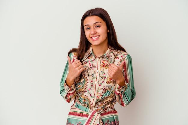 Jeune femme isolée sur un mur blanc levant les deux pouces vers le haut, souriant et confiant