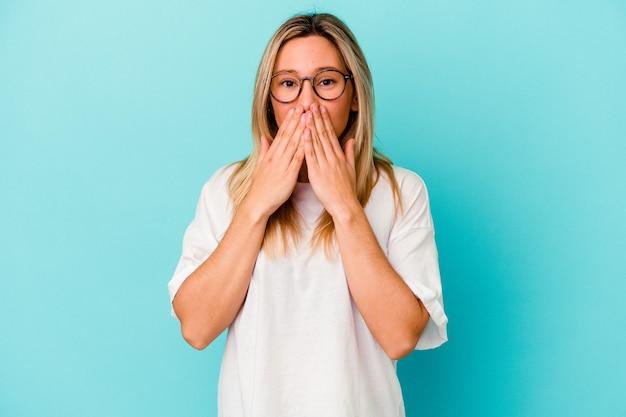 Jeune femme isolée sur un mur bleu choqué, couvrant la bouche avec les mains, impatient de découvrir quelque chose de nouveau