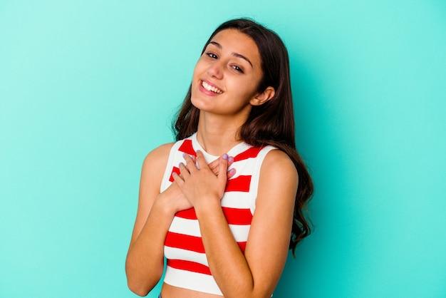 Jeune femme isolée sur un mur bleu a une expression amicale, appuyant sur la paume de la main contre la poitrine