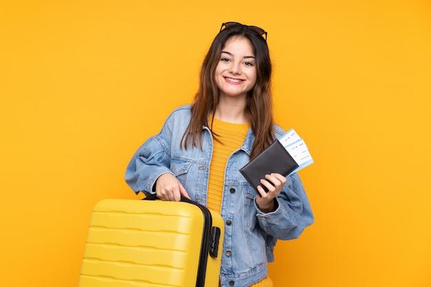 Jeune femme isolée sur un mur jaune en vacances avec valise et passeport