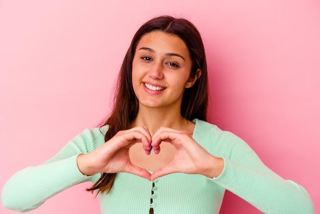 Jeune femme isolée sur un mur rose souriant et montrant une forme de coeur avec les mains