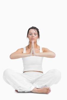 Jeune femme avec les jambes croisées en position de prière