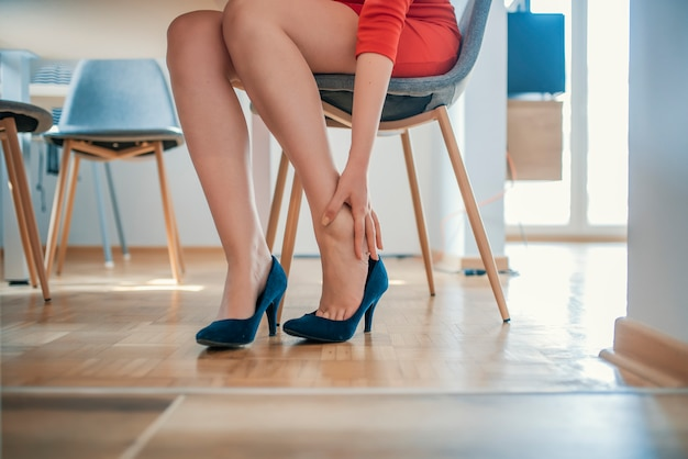 Jeune femme avec des jambes minces se sentir mal à cause de porter des talons hauts