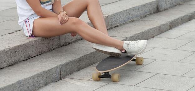 Jeune femme, jambes, skateboard, à, skatepark