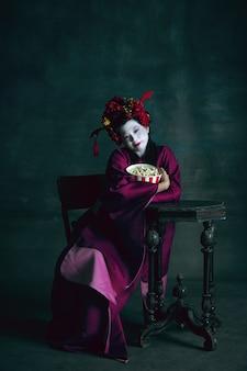 Jeune femme japonaise comme geisha sur vert foncé