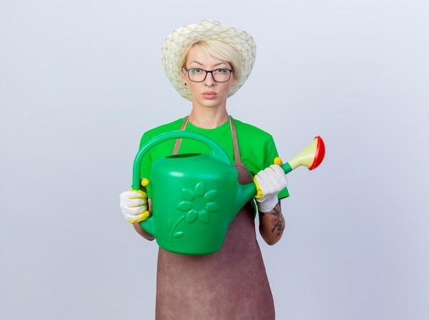 Jeune femme jardinier aux cheveux courts en tablier et chapeau tenant un arrosoir avec un visage sérieux