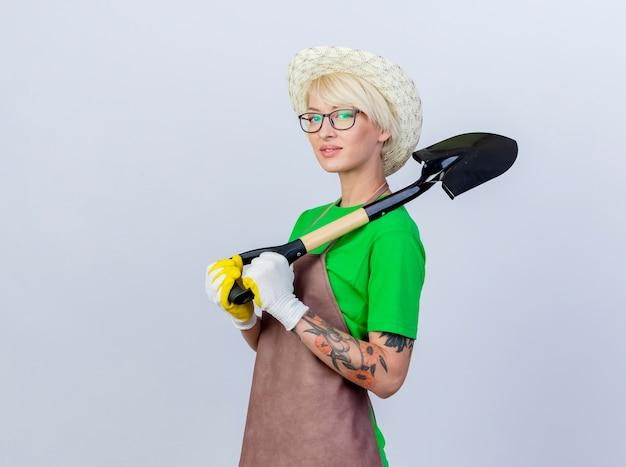 Jeune femme jardinier aux cheveux courts en tablier et chapeau tenant une pelle à la confiance en souriant