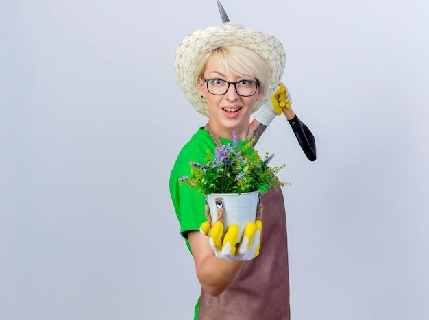 Jeune femme jardinier aux cheveux courts en tablier et chapeau tenant une pelle montrant une plante en pot avec un sourire sur le visage