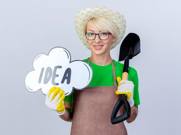 Jeune femme jardinier aux cheveux courts en tablier et chapeau tenant une pelle montrant un signe de bulle de parole avec une idée de mot souriant avec un visage heureux