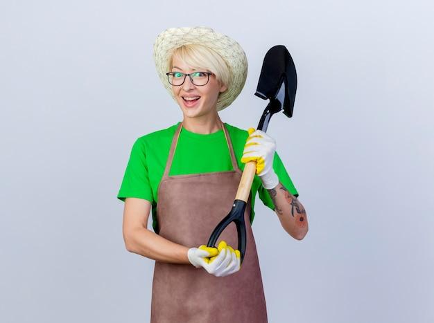 Jeune femme jardinier aux cheveux courts en tablier et chapeau tenant une pelle souriant gaiement