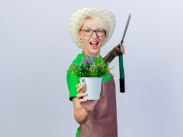 Jeune femme jardinier aux cheveux courts en tablier et chapeau tenant une tondeuse à haie montrant une plante en pot souriante avec un visage heureux