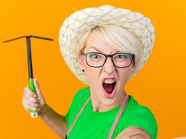 Jeune femme de jardinier aux cheveux courts en tablier et hat swinging mattock criant avec visage en colère frustré debout sur fond orange