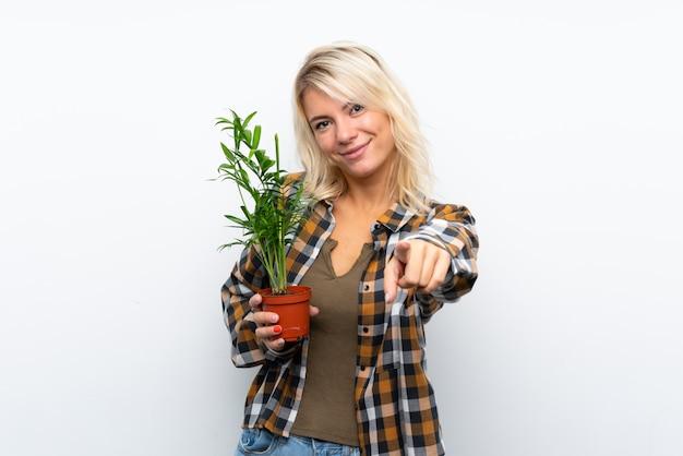 Jeune femme jardinier blonde tenant une plante sur des points blancs isolés, doigt avec une expression confiante