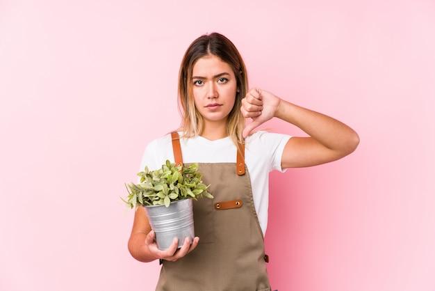 Jeune femme jardinier caucasien dans un fond rose montrant un geste d'aversion, les pouces vers le bas.