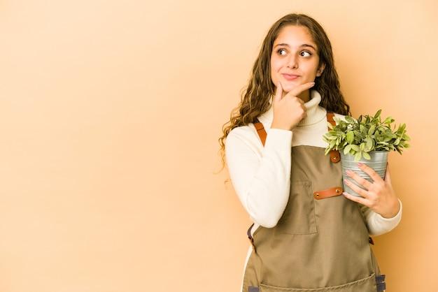Jeune femme de jardinier caucasien tenant une plante isolée à la recherche sur le côté avec une expression douteuse et sceptique.