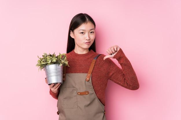Jeune femme jardinier chinois tenant une plante isolée se sent fière et sûre d'elle, exemple à suivre.
