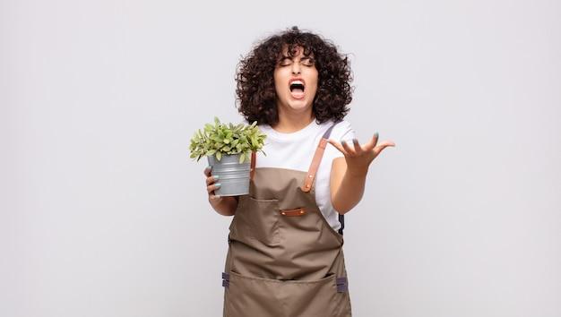 Jeune femme jardinier à la colère, agacé et frustré crier wtf ou quel est le problème avec vous