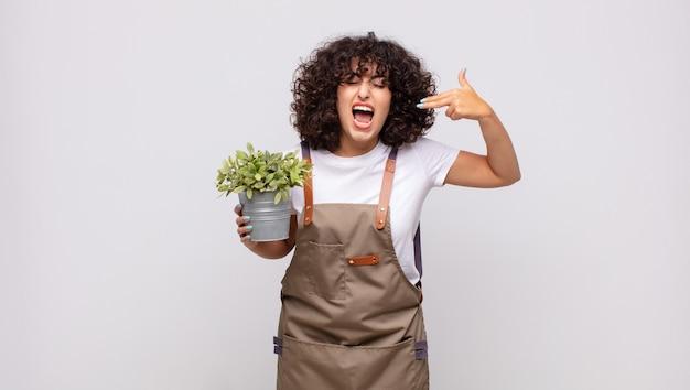 Jeune femme jardinier à la malheureuse et stressée, geste de suicide faisant signe de pistolet avec la main, pointant vers la tête