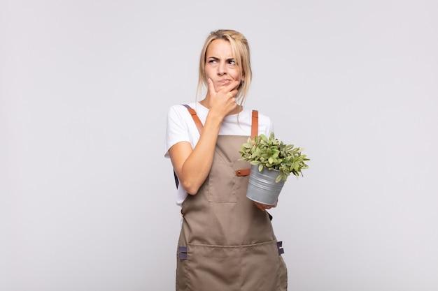 Jeune femme jardinier pensant, se sentant douteux et confus, avec différentes options, se demandant quelle décision prendre