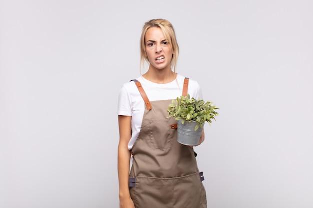 Jeune femme jardinier perplexe et confus, avec une expression stupide et stupéfaite en regardant quelque chose d'inattendu