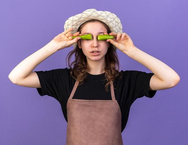 Jeune femme jardinier portant un chapeau de jardinage mettant le poivre cassé sur les yeux