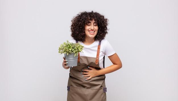 Jeune femme jardinier riant à haute voix à une blague hilarante, se sentir heureux et joyeux, s'amuser