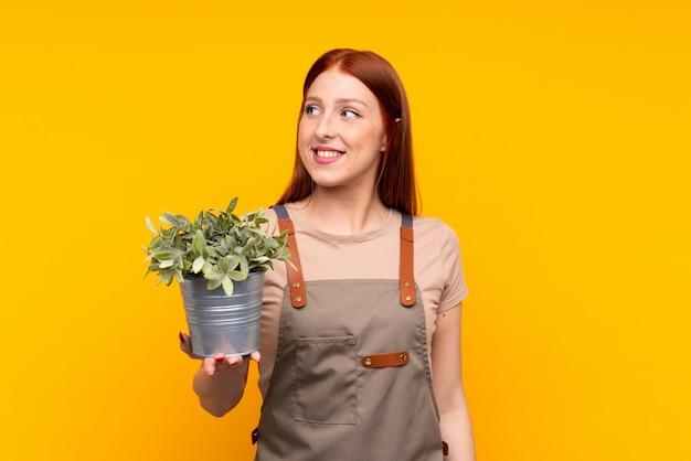 Jeune femme jardinier rousse tenant une plante sur rire jaune isolé