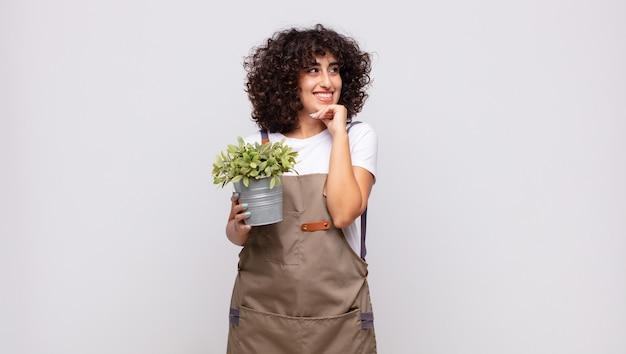 Jeune femme jardinier souriant joyeusement et rêvassant ou doutant, regardant sur le côté