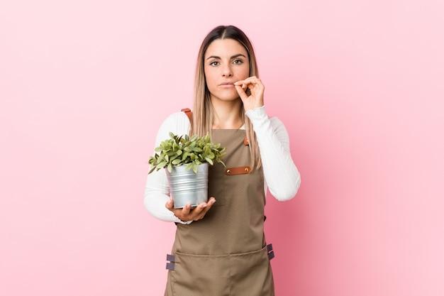 Jeune femme jardinier tenant une plante avec les doigts sur les lèvres en gardant un secret.