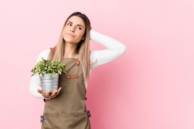 Jeune femme jardinier tenant une plante touchant l'arrière de la tête, pensant et faisant un choix.