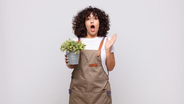 Jeune femme jardinier à très choqué ou surpris, regardant la bouche ouverte en disant wow