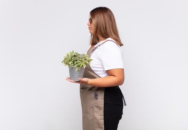 Jeune femme jardinier sur vue de profil à la recherche de copier l'espace à venir, penser, imaginer ou rêver